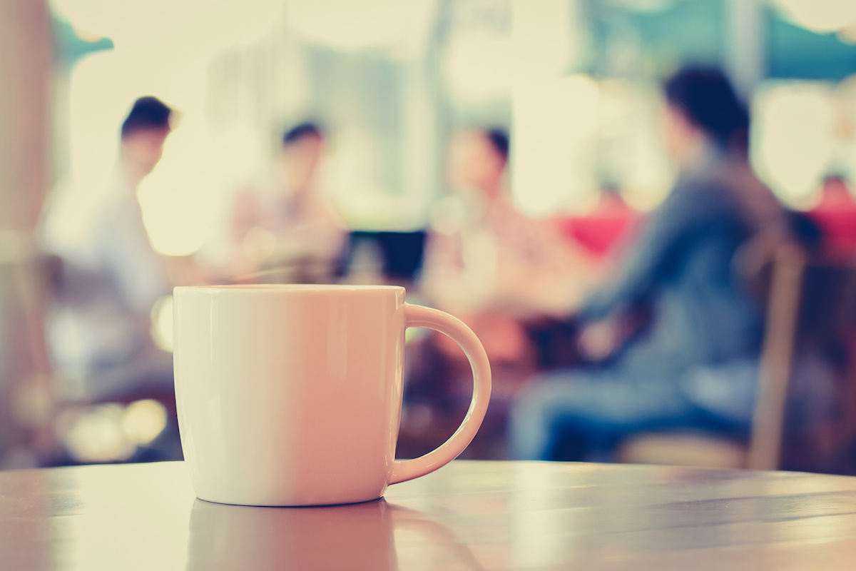 Coffee cup on the table with people in coffee shop as blur background - vintage (retro) style color effect